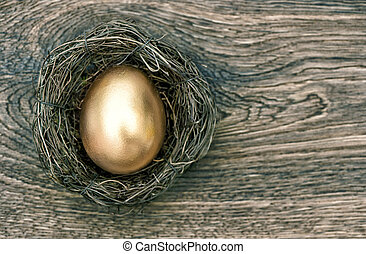 golden easter egg in nest on wooden background