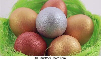 Golden Easter eggs in green basket. Close up.
