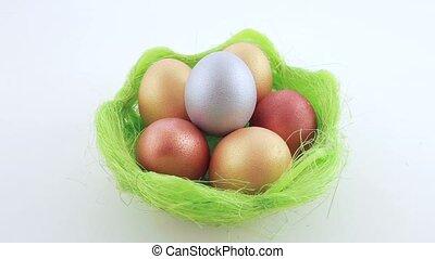 Golden Easter eggs in green basket. White background