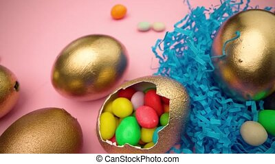 Golden eggs with scattered sweets for Easter on pink background
