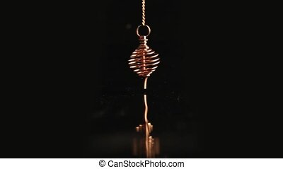 Golden energy pendulum in the form of a spiral swings against a black background