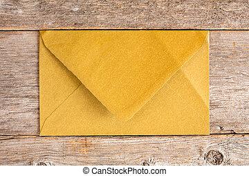 Golden envelope over wooden background.