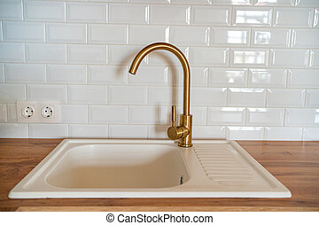 Golden faucet in the kitchen. sink for washing dishes.