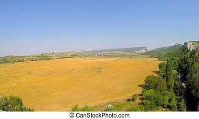 Golden Field With Agricultural Machinery - WIDE SHOT of a...