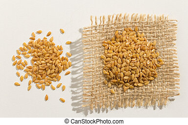 Golden Flax Seed. Close up of grains spreaded over white table.