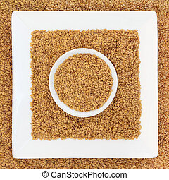 Golden linseed flax seed in square and round porcelain dishes.