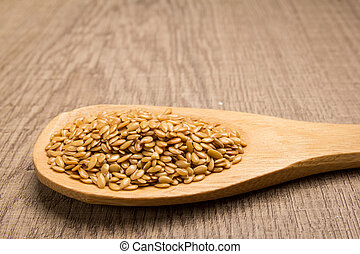 Golden Flax seed. Grains in wooden spoon. Rustic.