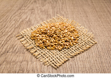 Golden Flax seed. Grains on square cutout of jute. Wooden table. Selective focus.