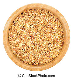 Golden flax seeds in wooden bowl isolated.