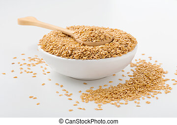 Golden flaxseed in wooden spoon and bowl