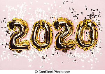Golden foil balloons 2020 and sparkles on pink pastel background. Christmas concept
