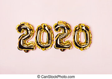 Golden foil balloons on pink pastel background. Inflatable numbers 2020. Christmas concept