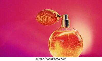 Golden fragrance bottle and shining light flares on pink ...