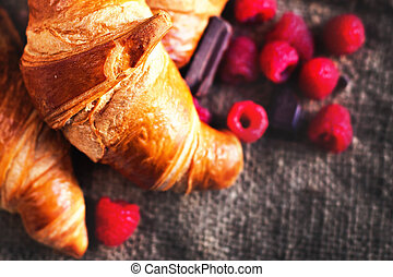 Golden fresh croissants on old wooden background close up with raspberry