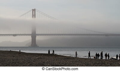 Golden gate bridge with fog and people on a sandy beach