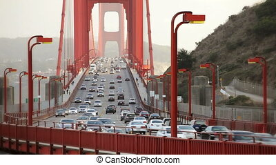 Pedestrians walking and cars driving over the Golden Gate Bridge