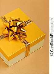 Golden gift box on the beige tablecloth