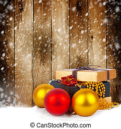 Golden gift box with Christmas balls and garlands of beautiful beads on wooden background