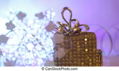 Golden gift box with snowflake. Decoration for Christmas winter holidays, present with abstract bokeh shiny glowing blur lights background