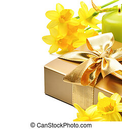 Golden gift box with springtime narcissus over white