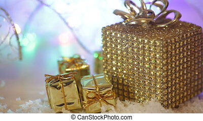 Golden gift boxes with snow and ribbon. Decoration for Christmas winter holidays, present with abstract bokeh shiny glowing blur lights background