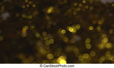 Golden glitters blurred background with shiny bokeh from...