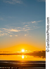 Golden glow of sunrise across bay clouds and silhouette on ...
