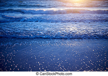 Golden glow of sunset over gently lapping waves