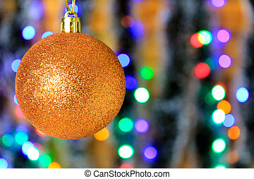 Golden hanging ball, christmas decoration with blurred lights background.