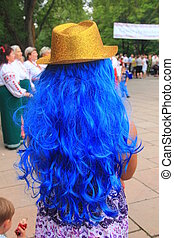 Golden hat on a blue wig of a young girl