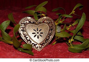 Golden heart and mistletoe on red background