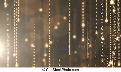 Animation of golden star light strands falling in hypnotic motion in seamless loop with lens flare and bokeh spots on dark background. Light, colour and movement concept digitally generated image.
