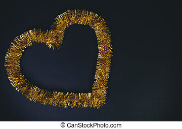 Golden heart shape over black background. Love and carnival concept.
