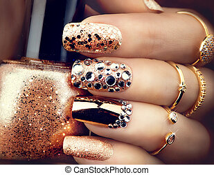 Golden holiday style bright manicure with gems and sparkles....