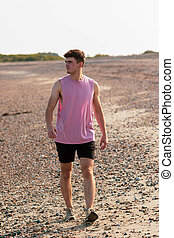 Young caucasian man walking on a beach at golden hour wearing a sleeveless shirt and black shorts