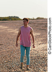 Young caucasian man walking on a beach at golden hour wearing a sleeveless shirt and jeans