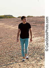 Young caucasian man walking on a beach at golden hour wearing a t-shirt and jeans