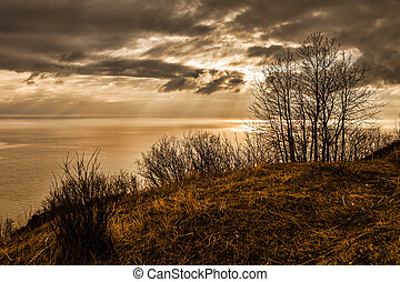 Golden light at sunset with storm clouds over the bay and stark winter landscape.
