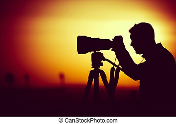 Golden Hour Photography. Silhouette of Men Taking Pictures with Large Telephoto Lens.