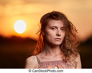 Portrait of a beautiful young woman in retro dress in the sunset at golden hour