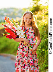 Golden hour portrait of a cute little girl of 8 years old, holding colorful gladiolas flowers, vertical image