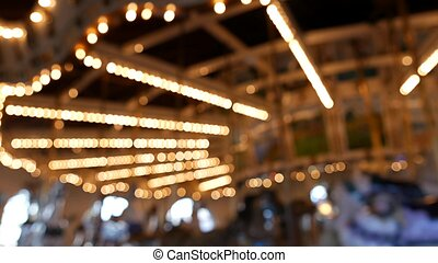Golden illuminated defocused retro carousel turning in amusement park. Blurred shiny merry-go-round glowing and rotating at night. Radiant spinning symbol of childhood. Festival atmosphere of funfair