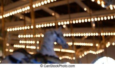 Golden illuminated defocused retro carousel turning in ...