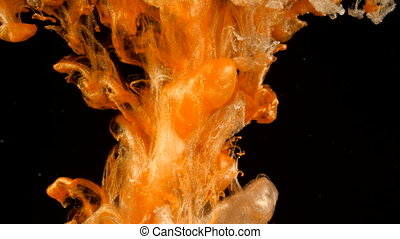 Golden ink in water. Gold and white drops of paint reacting,...