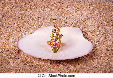Golden jewelry in shell on sand