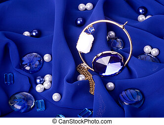 Golden jewelry on blue background
