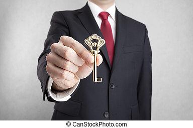Golden key in businessman hand