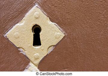 Golden keyhole in a brown door