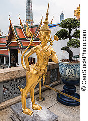 Golden Kinnari statue at temple, Wat Phra Kaew in Grand Palace, B