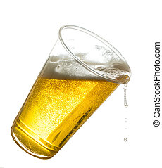 Golden beer, ale or lager in a tilting plastic disposable cup or glass with beer spilling over edge of pint glass